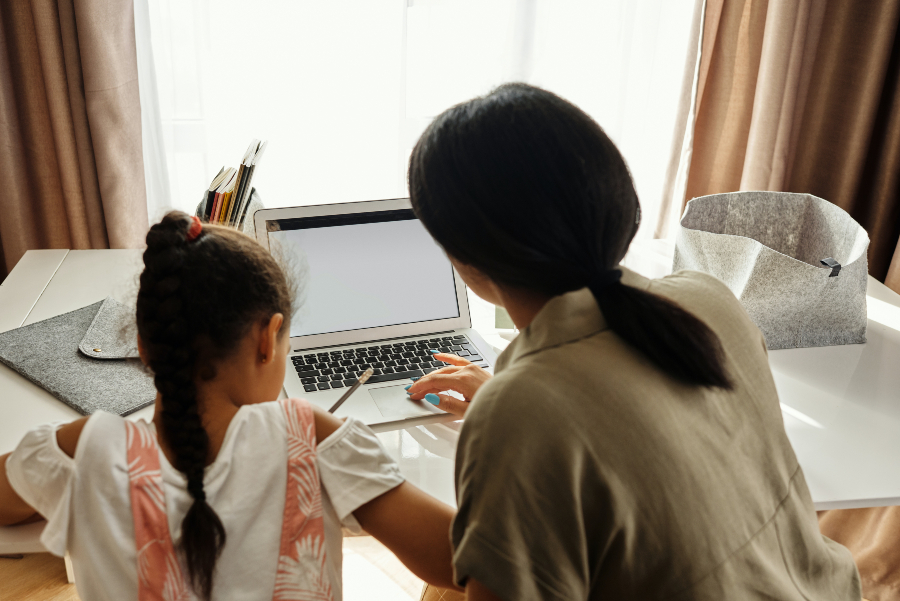 Woman and child sit at a computer to do online home schooling together