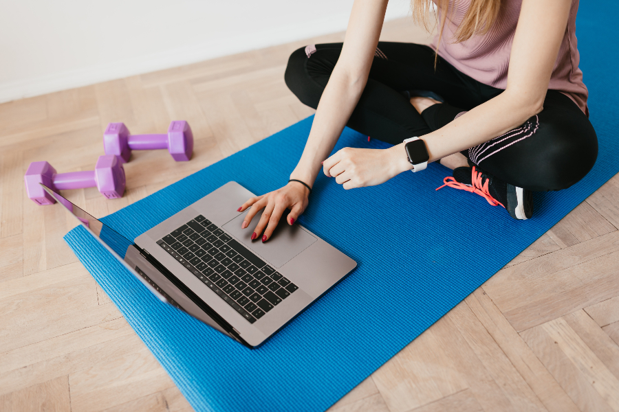 Woman on exercise mat gets ready to do online fitness class